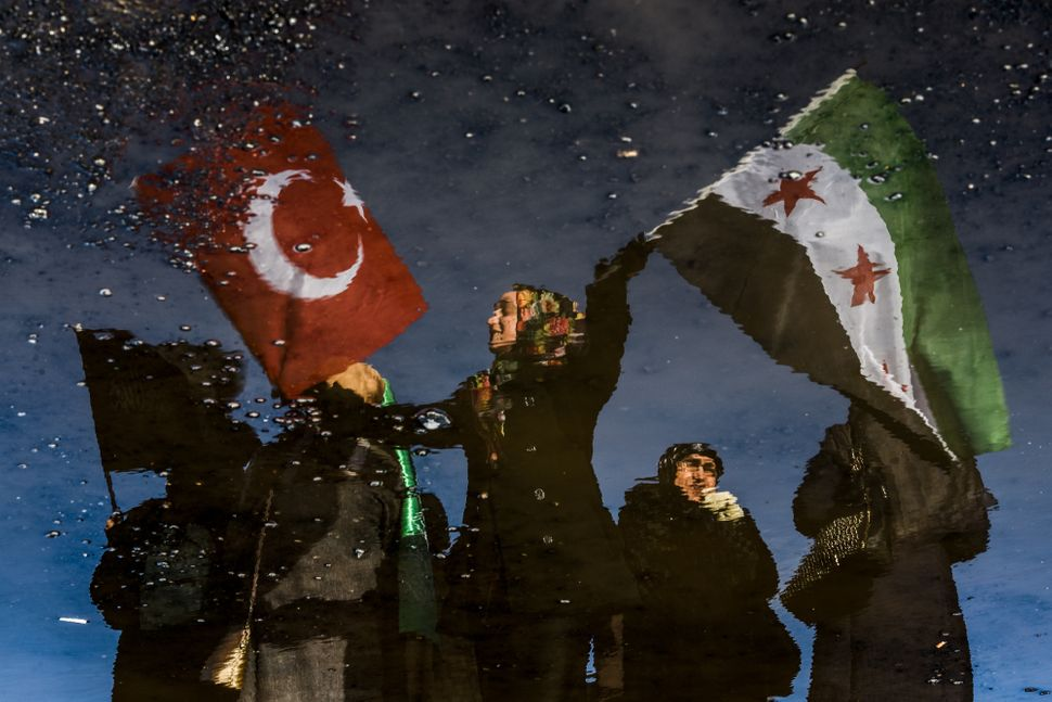 A reflection shows a woman waving Turkish and Free Syrian flags as an aid convoy to Aleppo organized by IHH Humanitarian Reli