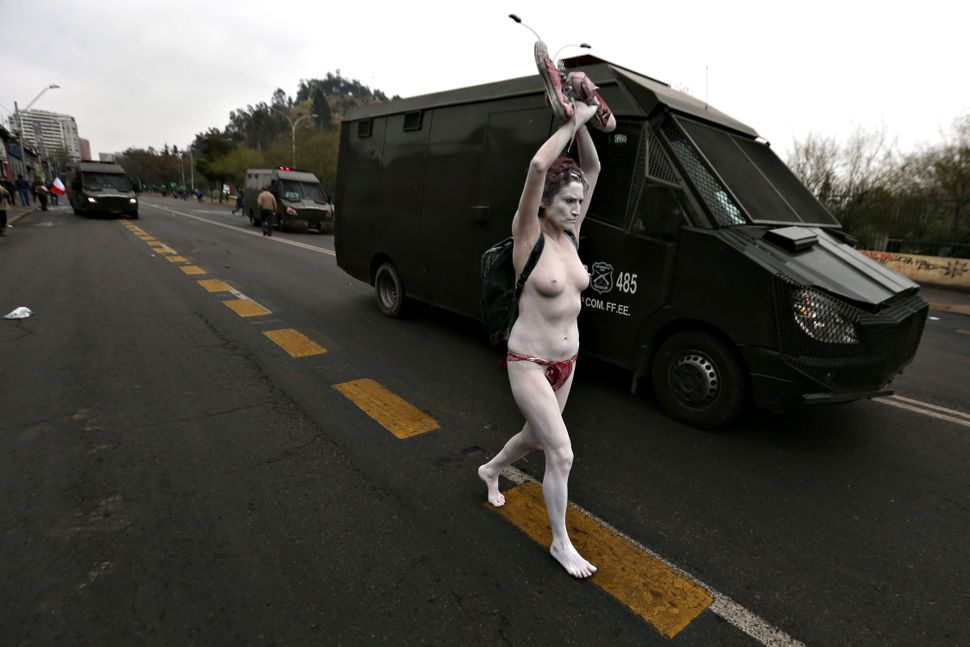A half-naked demonstrator runs alongside a riot police vehicle as Human Rights activists march in Santiago, on Sep. 11, 2016