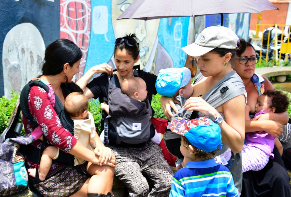 Women -- some of them breastfeeding -- carry out a 'mamaton' (from Spanish 'amamantar' ,breastfeed, and 'marathon') outside t