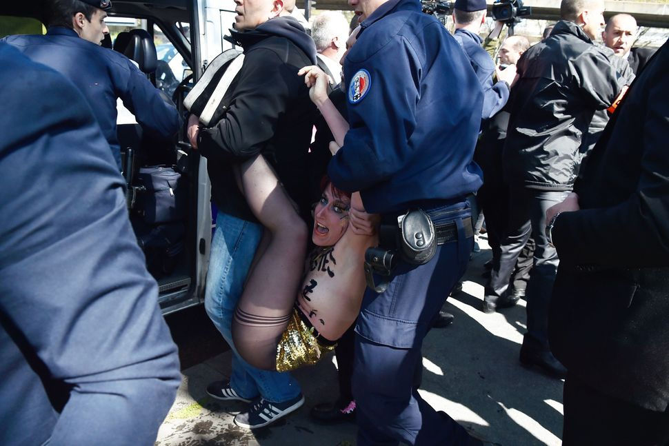 French police officers detain a topless Femen activist during a protest outside a banquet held by France's far-right Front Na