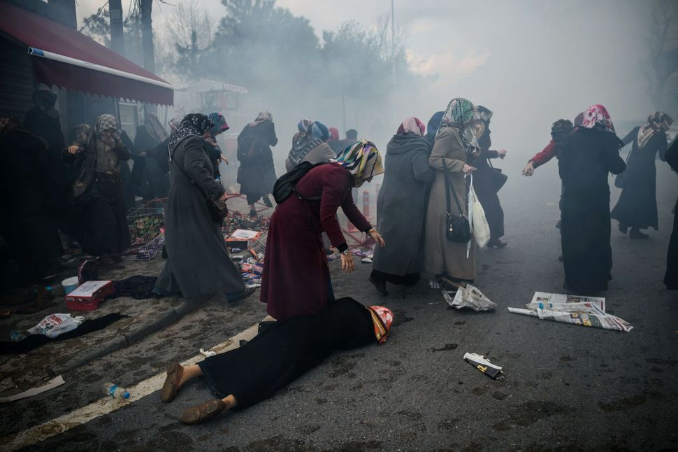 Women helps another woman who fell as Turkish anti-riot police officers launch tear gas to disperse supporters in front of th