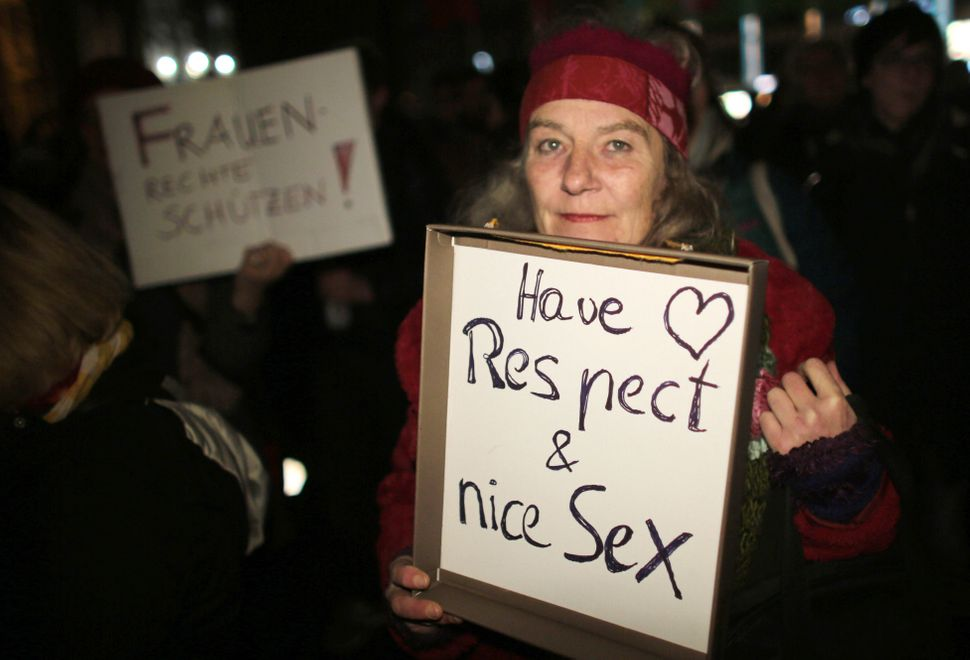 A woman holds a sign reading 'Have respect and nice sex' during a demonstration in Cologne on Jan. 5, 2016. German leaders ex