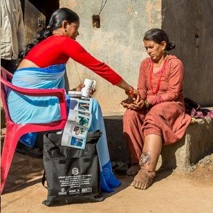 An FCHV in Nepal provides information and treatment to a woman with lymphatic filariasis, a type of NTD.
