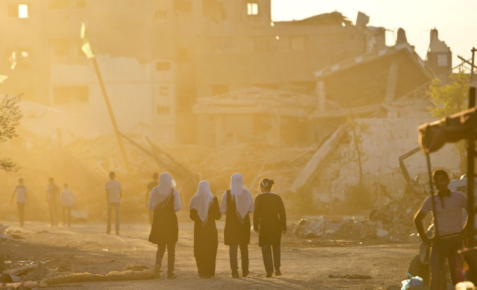 Palestinian girls walk past buildings which were destroyed by Israeli strikes on their way to school in the Shejaiya neighbou