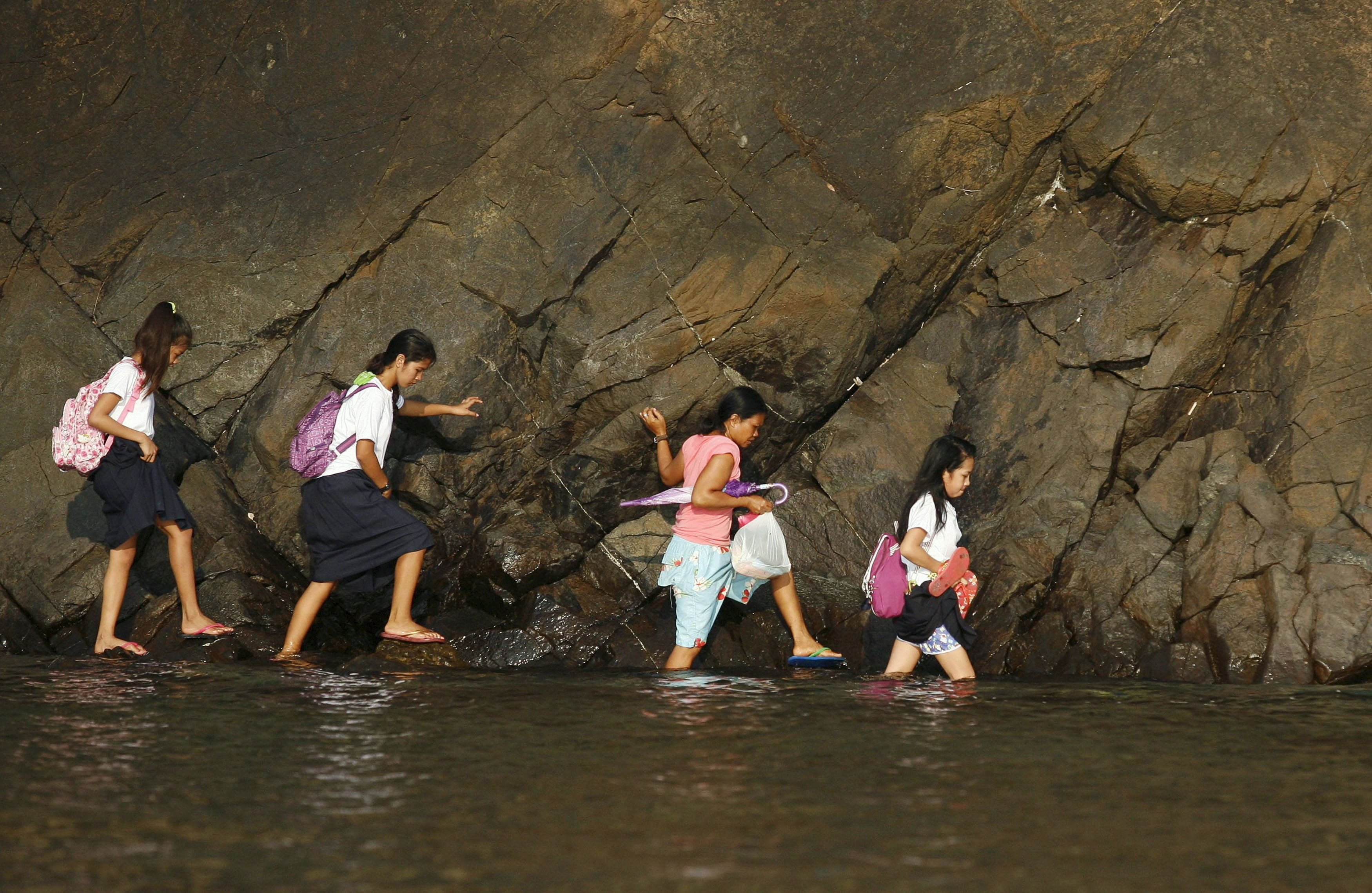 A woman accompanies some students as they wade in the shallow part of a rocky beach to their school to attend the first day o