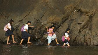 A woman accompanies some students as they wade in the shallow part of a rocky beach to their school to attend the first day of classes in Sitio Kinabuksan,  Kawag village, Subic, Zambales Province, north of Manila June 1, 2015. An estimated 24 million public school students in the primary and secondary levels attend the opening of classes nationwide, local media reported. REUTERS/Lorgina Minguito           TPX IMAGES OF THE DAY