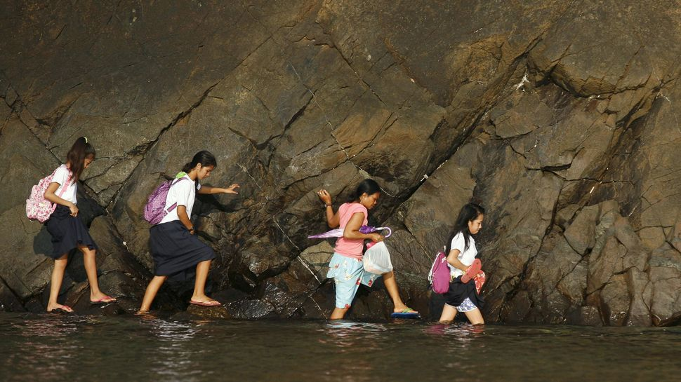 Young girls wade through water to get to school in Manila, Philippines.