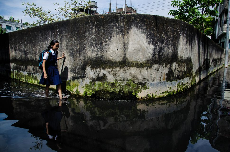 A school going girl walks through a water logged street in Dhaka, Bangladesh, 01 October 2013. Climate change in Bangladesh i