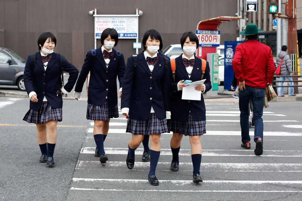 School girls, wearing surgical masks, cross a street at lunch time in Kyoto, western Japan November 19, 2014.