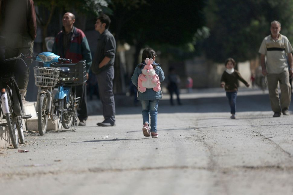 A girl carrying a school bag walks in eastern al-Ghouta, near Damascus October 21, 2014.