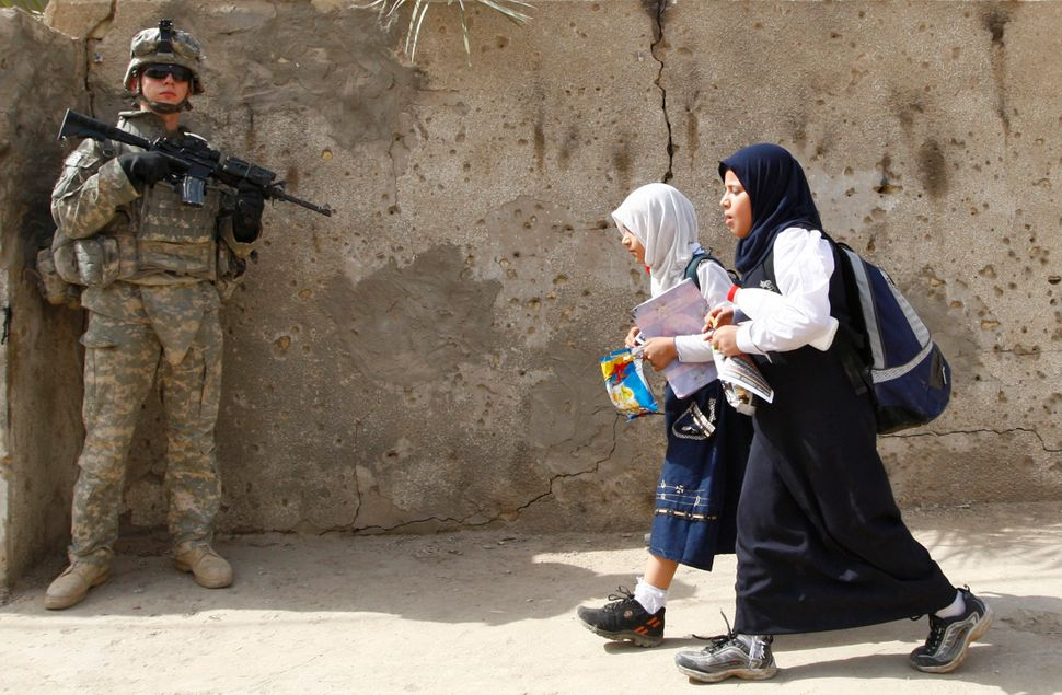 Girls walk past a U.S. soldier on a patrol with the Iraqi police in Baghdad's Ameen district, Oct. 14, 2008.