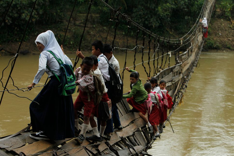 Students hold on to the side steel bars of a collapsed bridge as they cross a river to get to school at Sanghiang Tanjung vil