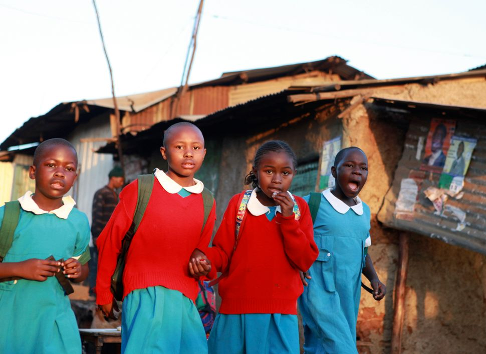 Girls walk to school during the early morning in the Kibera slums in Kenya's capital Nairobi February 15, 2013.