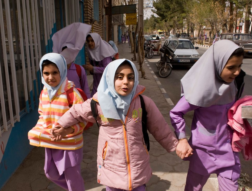 School girls walk down the street in Iranian President Mahmoud Ahmadinejad's birth village of Aradan, east of Tehran, March 1