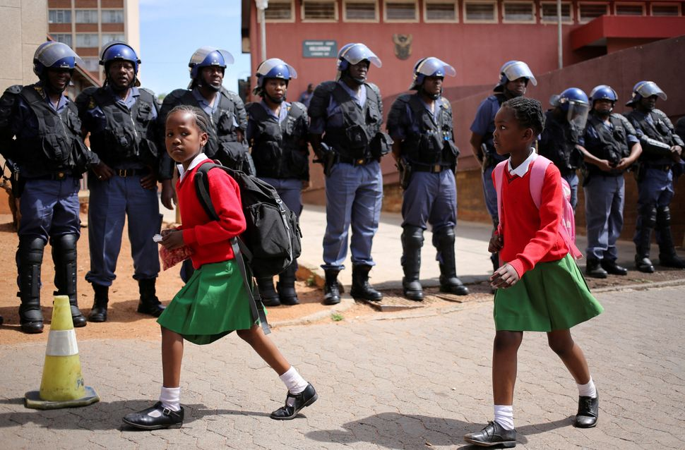 School girls walk past riot police standing guard outside Hillbrow magistrate court during an appearance of students who were