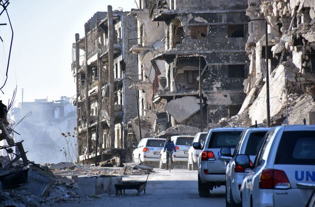 A UN convoy drives past damaged buildings in the eastern neighborhoods of