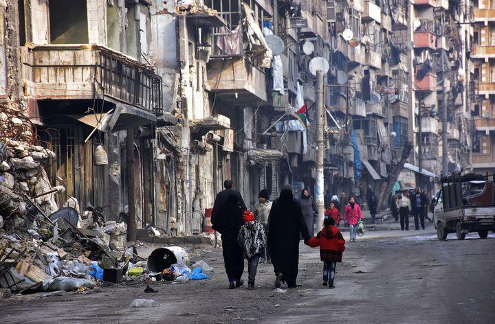 Syrians walk along a damaged street in Aleppo's formerly rebel-held al-Shaar neighborhood.