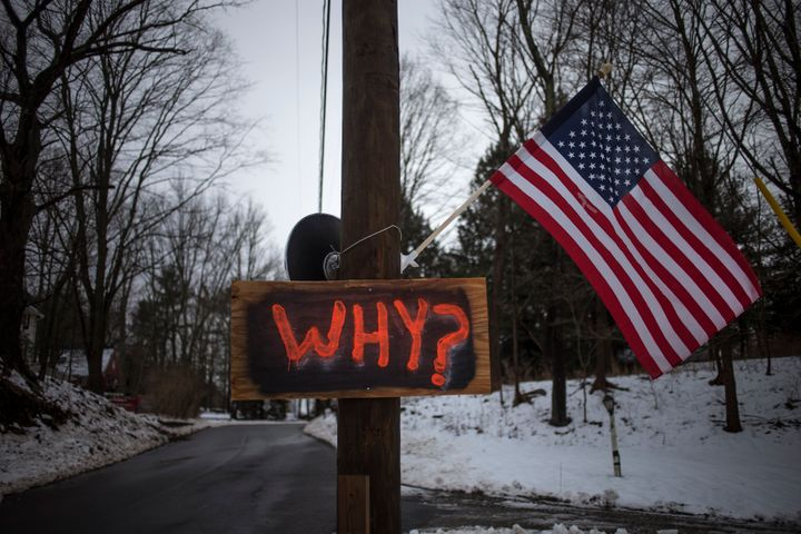 A sign is posted on an electricity pole outside a house near Sandy Hook Elementary School, nearly two weeks after a gunman sh