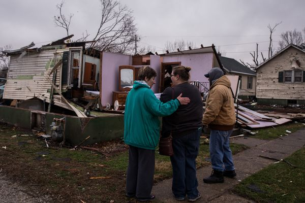 Resident Nancy Warner, center, gets a hug from Sherry Pagakis as she surveys tornado damage to her house on Wednesday, March