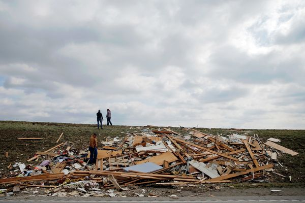 Grant Huber, Susan Krauss, and Michelle Naeger look through wreckage downwind and across the street from Pat Huber's home on