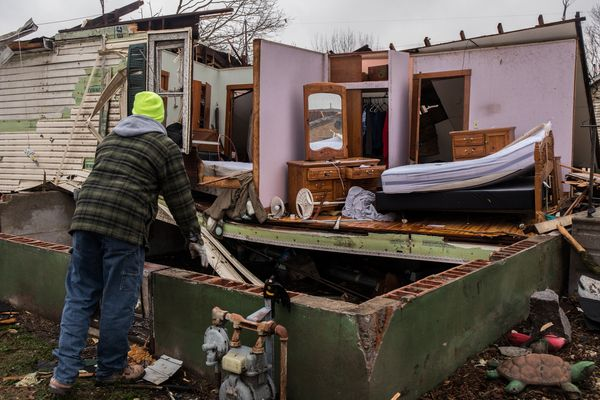 Mike Small, brother of resident Nancy Warner, surveys tornado damage to her house on Wednesday, March 1, 2017 in Naplate, Ill