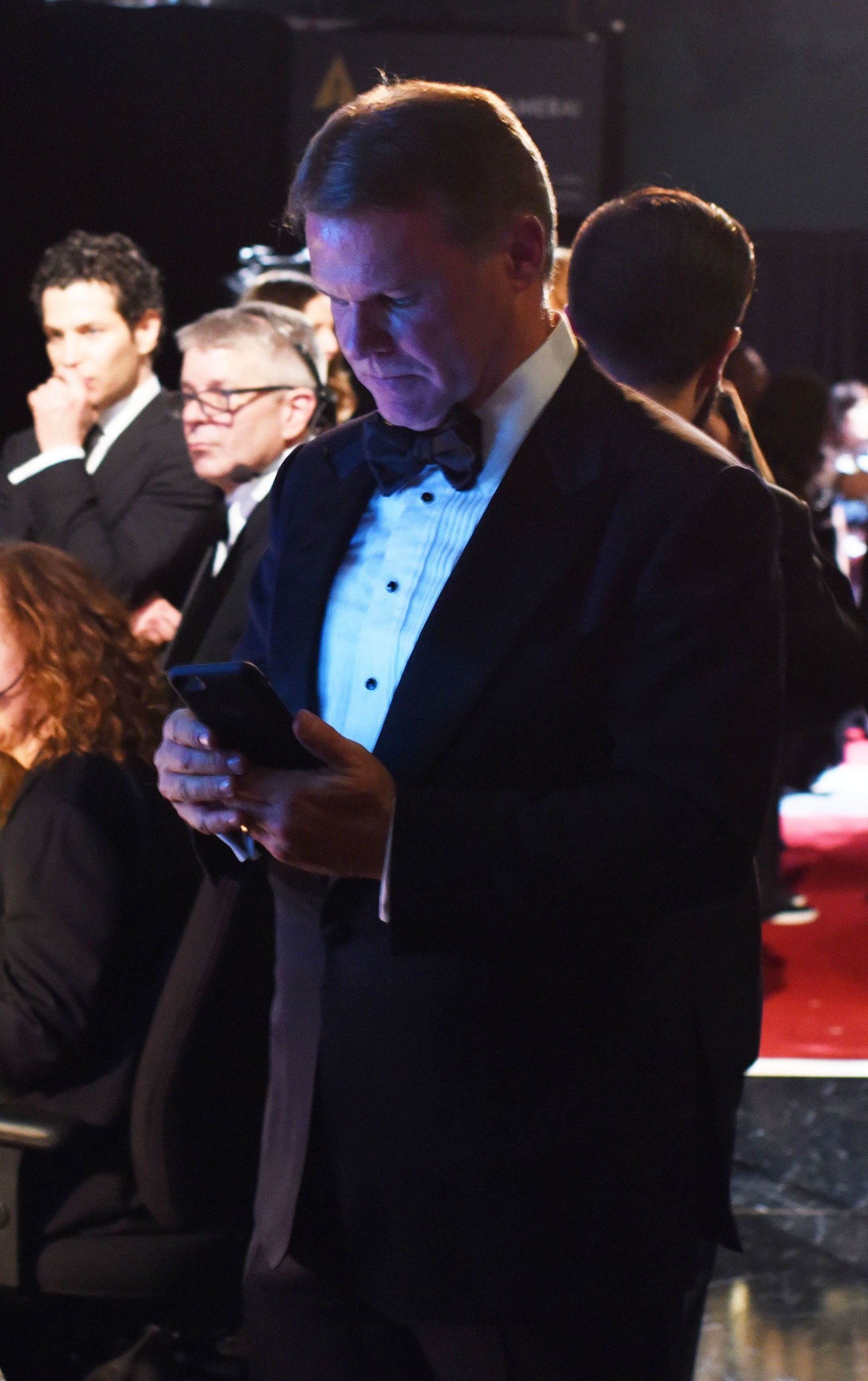 Brian Cullinan using his phone backstage at 9:04pm PST at the 89th annual Academy Awards.