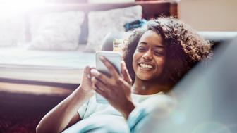A photo of young woman using mobile phone. Female is smiling while holding smart phone. She is lying on sofa at home.