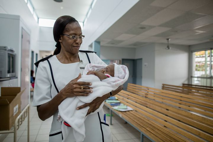 <p>Today the waiting room at Onandjokwe's Shanamutango HIV clinic isn't crowded. Wait times have dropped drastically since the hospital hired additional staff and began making services available beyond the central hospital location. Here nurse Ruusa Shipena holds an HIV-negative infant while the baby's mother receives care. </p>
