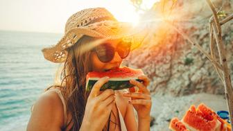 young woman having fun and eating juicy fresh watermelon outdoor at sunset time with snuffler in summer time