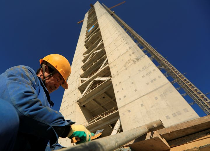 A Chinese worker is seen below a minaret at the construction site of the new Great Mosque of Algiers, which is bein