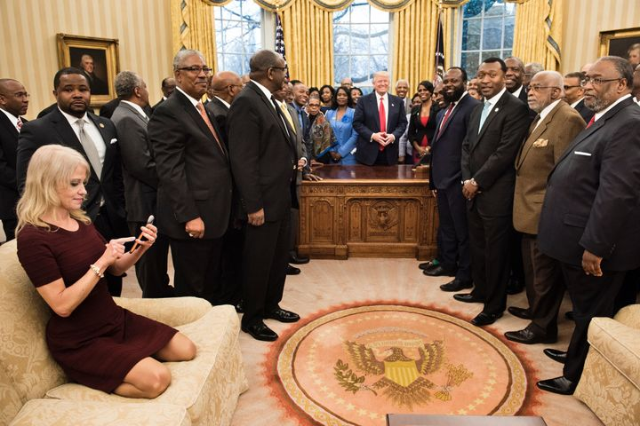 Kellyanne Conway checks her phone after taking a photo in the Oval Office. Some took issue with the photo, calling her pose t