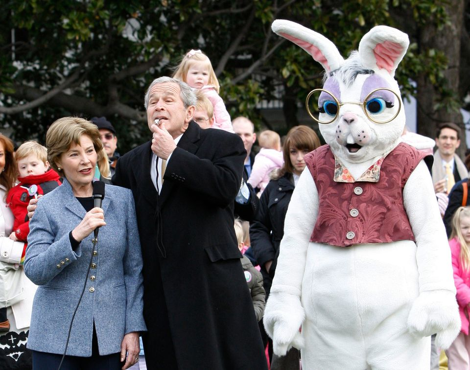 President George W. Bush, flanked by first lady Laura Bush and a person dressed as the Easter Bunny, blows a whistle to offic