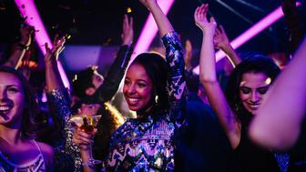 Happy afro american young woman dancing with her friends while on a night club party with confetti and holding a drink on her hand
