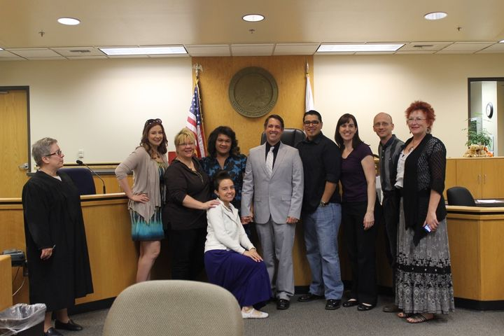 "Adoption finalization at the Sacramento County Court in April 2014; Erica and Scott are surrounded by Erica's ""posse,"" her in"