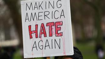 """A demonstrator holds a banner that reads """"Making America Hate Again"""", during a march against U.S. President Donald Trump and his temporary ban on refugees and nationals from seven Muslim-majority countries from entering the United States, in London, Britain, February 4, 2017. REUTERS/Neil Hall"""