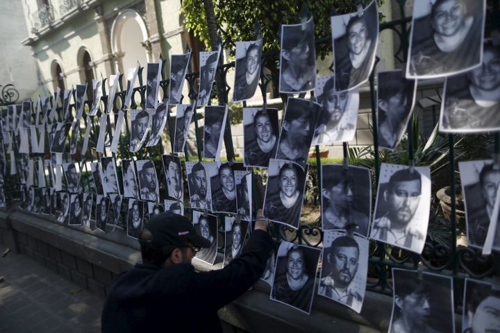 A man hangs images of murdered journalists outside the Government of Veracruz building in Mexico City, Feb. 11, 2016. Mexico