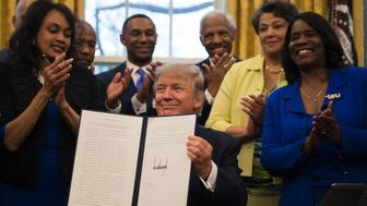 US President Donald Trump (C) holds up an executive order to bolster historically black colleges and universities (HBCUs) after signing it in the Oval Office of the White House in Washington, DC, February 28, 2017. / AFP / JIM WATSON        (Photo credit should read JIM WATSON/AFP/Getty Images)