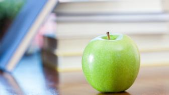 Green apple on desk in front of stack of books in classroom.