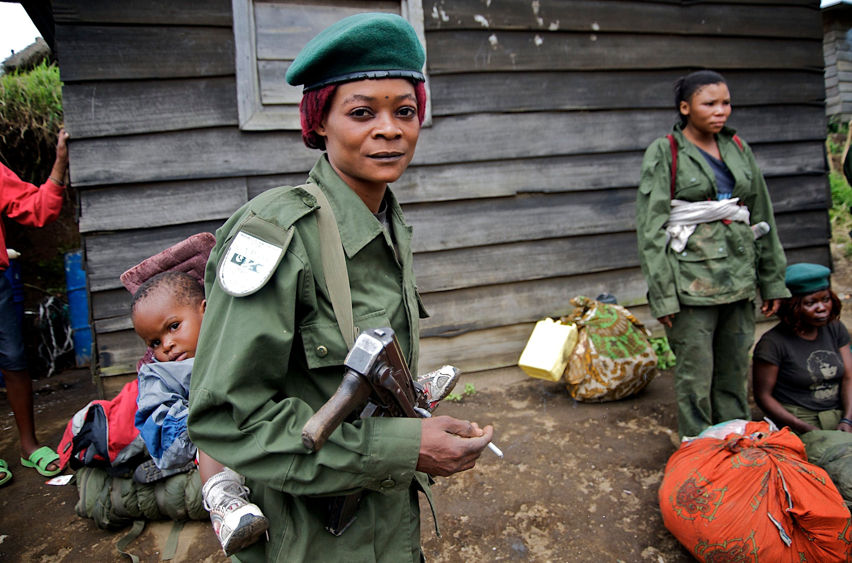 A government soldier carries her infant on her back at Mushake in eastern Congo, January 26, 2009. Congolese Hutu rebels said on Sunday they had clashed for the first time with a Rwandan-Congolese force deployed to crush them and civilians expressed fears they would be caught up in the violence. REUTERS/Alissa Everett (DEMOCRATIC REPUBLIC OF CONGO)   BEST QUALITY AVAILABLE