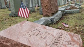 An American flag still stands next to one of over 170 toppled Jewish headstones after a weekend vandalism attack on Chesed Shel Emeth Cemetery in University City, a suburb of St Louis, Missouri, U.S. February 21, 2017.  REUTERS/Tom Gannam TPX IMAGES OF THE DAY
