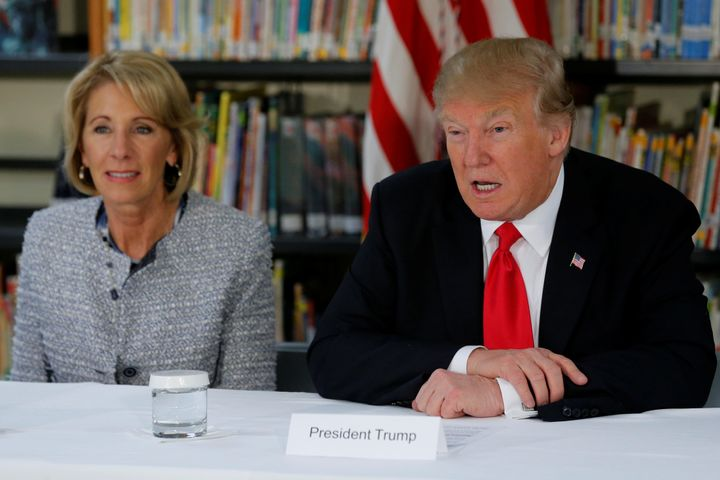 U.S. President Donald Trump (R) and Education Secretary Betsy DeVos (L) meet with parents and teachers at Saint Andrew Cathol