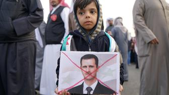 A boy holds a crossed out image of Syria's President Bashar al-Assad during a protest against Russia's role in Aleppo, across the street from the Russian Embassy compound in Shaab, Kuwait, December 14, 2016. REUTERS/Stephanie McGehee