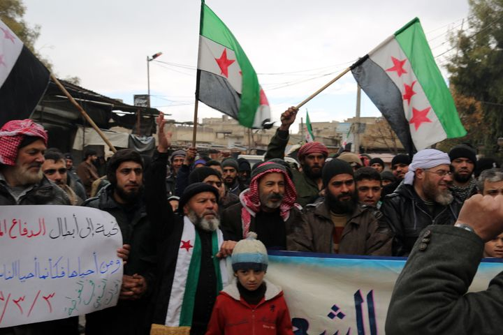 Syrians stage a protest against the Assad regime's violation of a cease-fire after Friday prayers in Damascus.