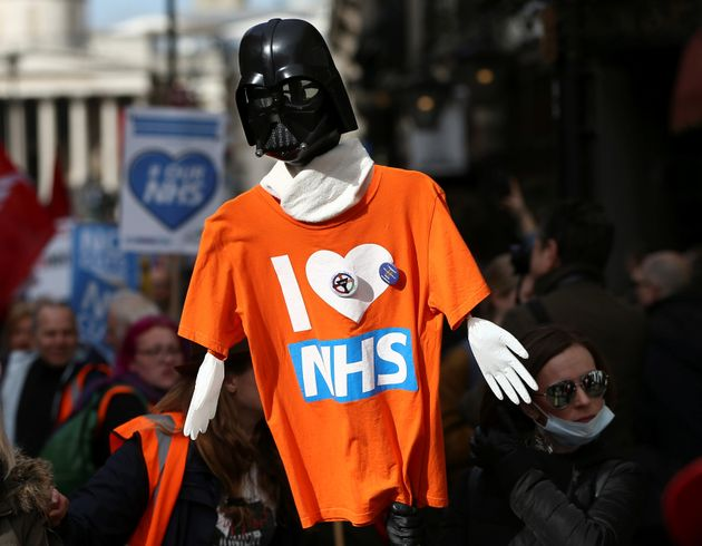 A Star Wars themed placard covered with a T-Shirt is held aloft during the NHS