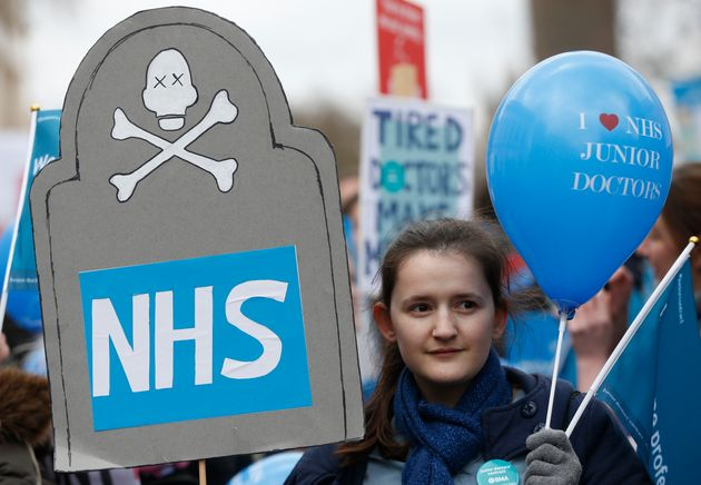 A demonstrator holds a balloon that reads 'I Love NHS Junior Doctors' during the