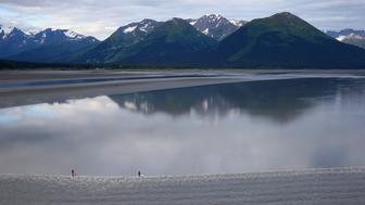 ANCHORAGE, AK - JULY 15:  A group of surfers ride the Bore Tide at Turnagain Arm on July 15, 2014 in Anchorage, Alaska. Alaska's most famous Bore Tide, occurs in a spot on the outside of Anchorage in the lower arm of the Cook Inlet, Turnagain Arm, where wave heights can reach 6-10 feet tall, move at 10-15 mph and the water temperature stays around 40 degrees Fahrenheit. This years Supermoon substantially increased the size of the normal wave and made it a destination for surfers.  (Photo by Streeter Lecka/Getty Images)