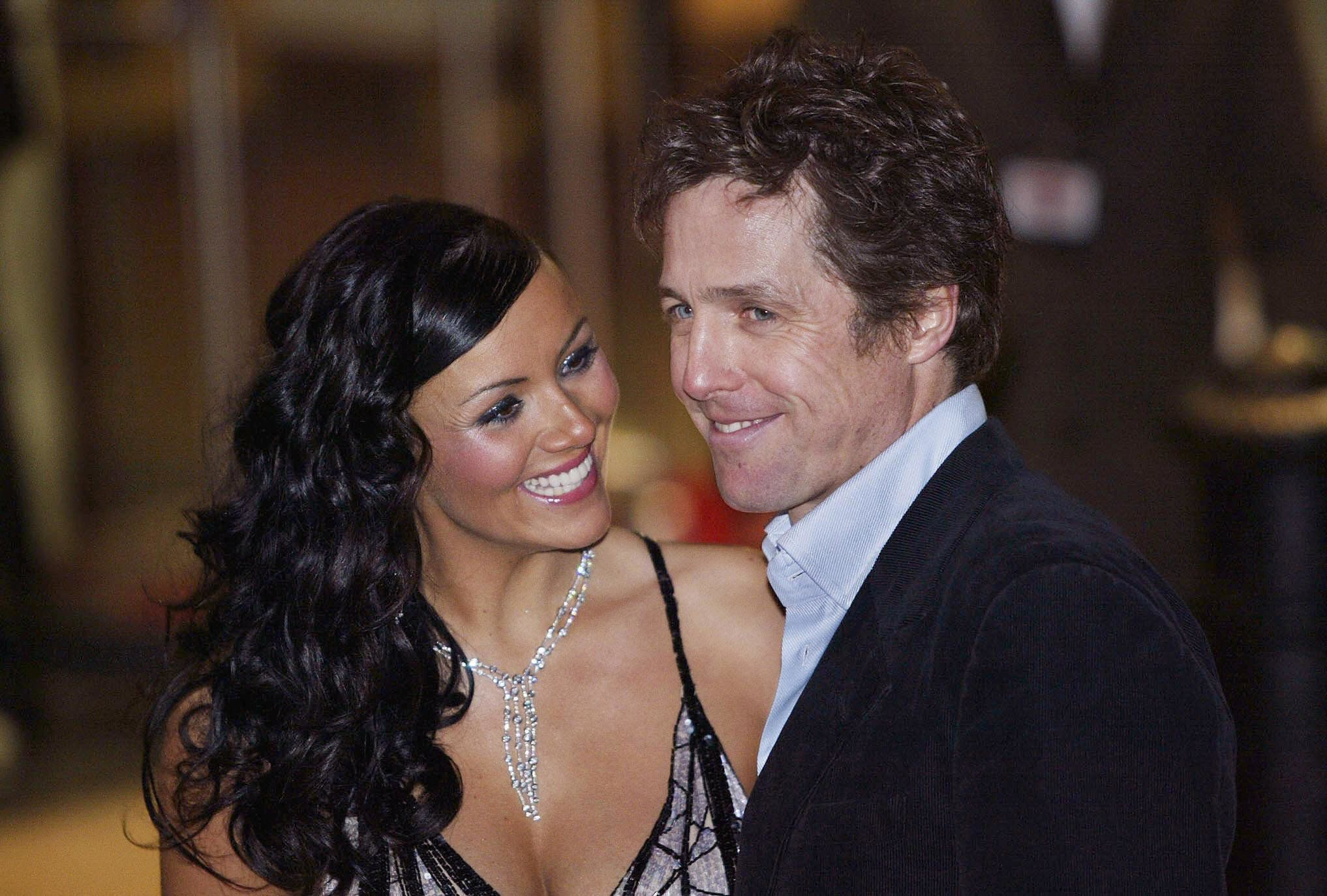 LONDON, UNITED KINGDOM:  Hugh Grant (R) and Martine McCutcheon arrive for the UK premiere of the film 'Love Actually', at the Odeon Cinema, Leicester Square in London, 16 November 2003. 'Love Actually' is the latest film from director Richard Curtis, who made 'Four Weddings and a Funeral' and 'Notting Hill'.  AFP PHOTO/ALESSANDRO ABBONIZIO  (Photo credit should read ALESSANDRO ABBONIZIO/AFP/Getty Images)