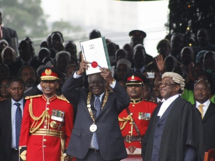 Former President Mwai Kibaki holds up the new constitution with a national seals during the promulgation of the new constitut