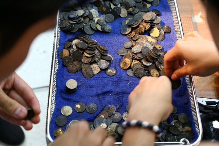 The coins, which altogether ended up weighing around 11 pounds, are seen being counted after their removal on Monday.