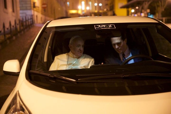 Pope Francis checks out the features of his new electric Nissan Leaf.